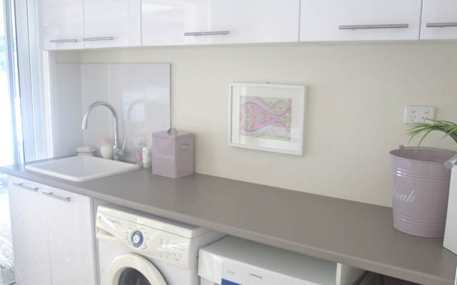 The perfect laundry with plenty of storage space and benchtops, and a dirty clothes basket